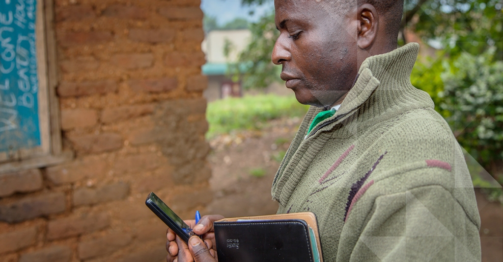 Community health worker checks on a patient's welfare using the Medic Mobile app on his cellphone